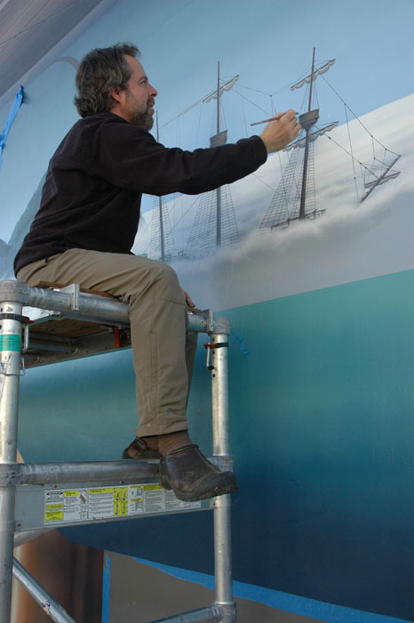 trompe l'oeil muralist john pugh painting a ship on scaffolding for a mural in santa cruz